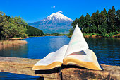 Open bible on top of a wooden parapet in front of the beautiful Mount Fuji. A beautiful blue sky day. Pages fluttering in the wind. Tanuki lake, Japan.