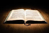 Old bible on a wooden table with dark background