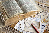 A bible on a wooden table, red pen, some notes