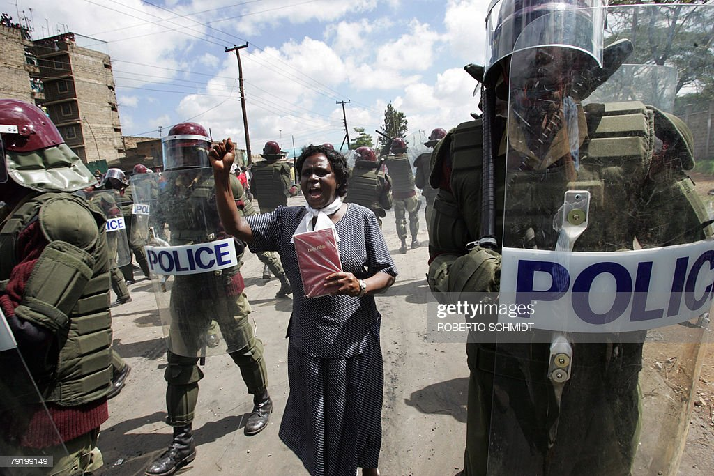 A bible toting Kenyan woman preaches as Kenyan riot police clear up a street from protestors in the Mathare slum in Nairobi, Kenya 30 December 2007. Kenyans expected to find out Sunday the winner of the country's tight presidential race, after three days of vote tallying marred by opposition claims of state-engineered rigging and widespread rioting.With only a few polling stations missing from the presidential tally, the electoral board was due to announce whether Mwai Kibaki would remain at the helm of East Africa's largest economy or Raila Odinga would become Kenya's fourth president.