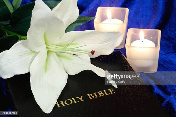 Bible with white lily and candles on blue