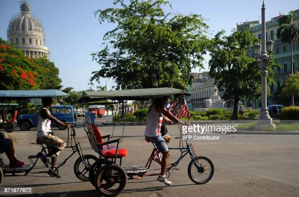 A bicitaxi with a US flag is seen in Havana on November 8 2017 Tighter restrictions on US travellers to Cuba will go into effect on Thursday...