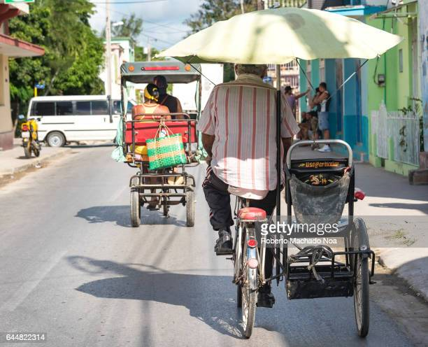 Bicitaxis or tricycles transporting passengers in city The sidecar like vehicle is only typical of Holguin city Economic hardship has made human...