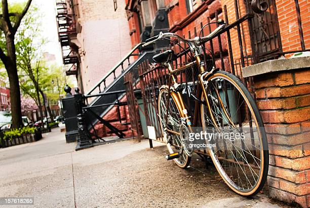 Bicycle against a gate on residential street in Manhattan