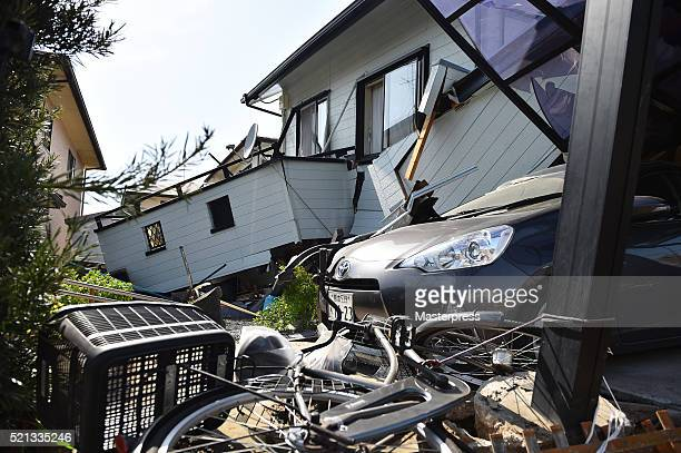 A bicycle and a car are seen by the collapsed house a day after the 2016 Kumamoto Earthquake on April 15 2016 in Mashiki Kumamoto Japan As of April...