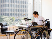 Bicycle by desk and businessman using laptop