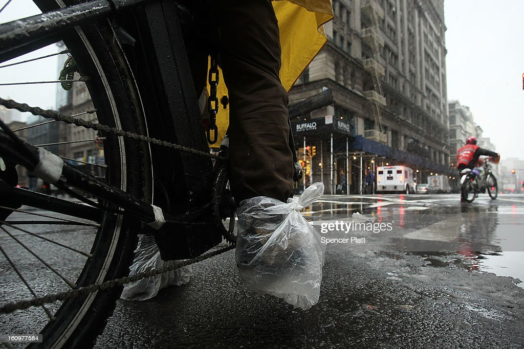 A bicycle delivery man has his feet wrapped in plastic as he rides through wind, snow and sleet on Broadway as Manhattan prepares for a major winter storm on February 8, 2013 in New York City. New York City and much of the Northeast is expected to get a foot or more of snow through Saturday afternoon with possible record-setting blizzard conditions expected. Heavy snow warnings are in effect from New Jersey through southern Maine.