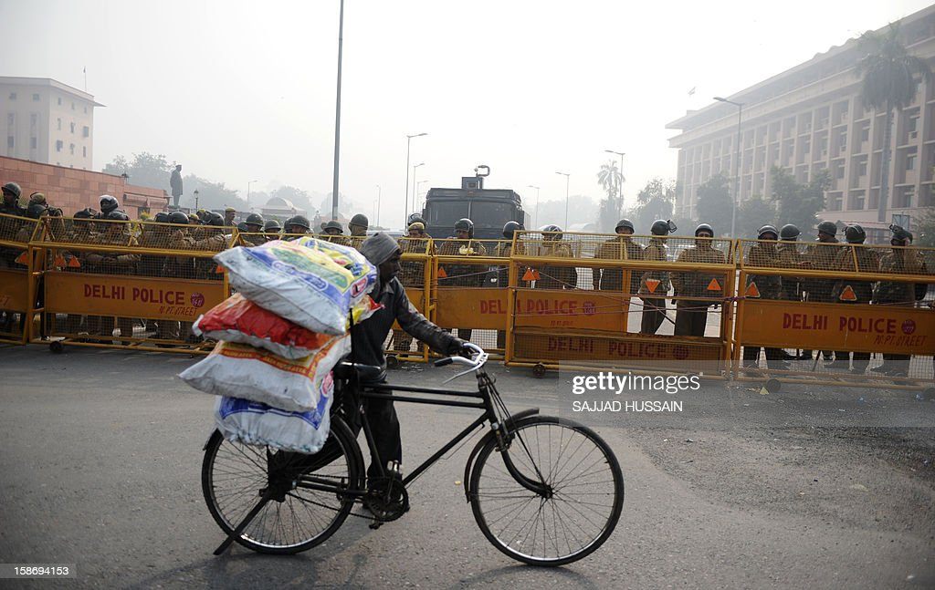 A bicycle deliveryman wheels his goods past Indian riot police keeping watch along a sealed-off road leading towards the landmark India Gate monument following weekend clashes between demonstrators and police in New Delhi on December 24, 2012. Indian Prime Minister Manmohan Singh has appealed for calm and vowed to protect women as police struggled to quell increasing outrage over sex crimes following the gang-rape of a student.