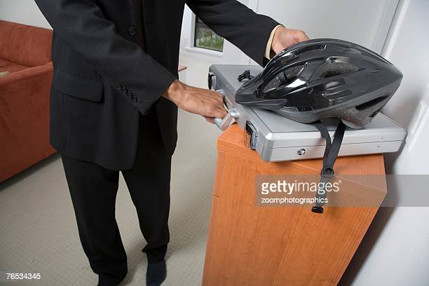 Bicycle helmet on briefcase with man in background