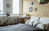 White city bicycle in bedroom with wooden wall