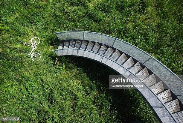 Bicycle in grass under spiral staircase
