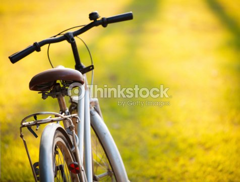 Bicycle in meadow during sunset : Stock Photo
