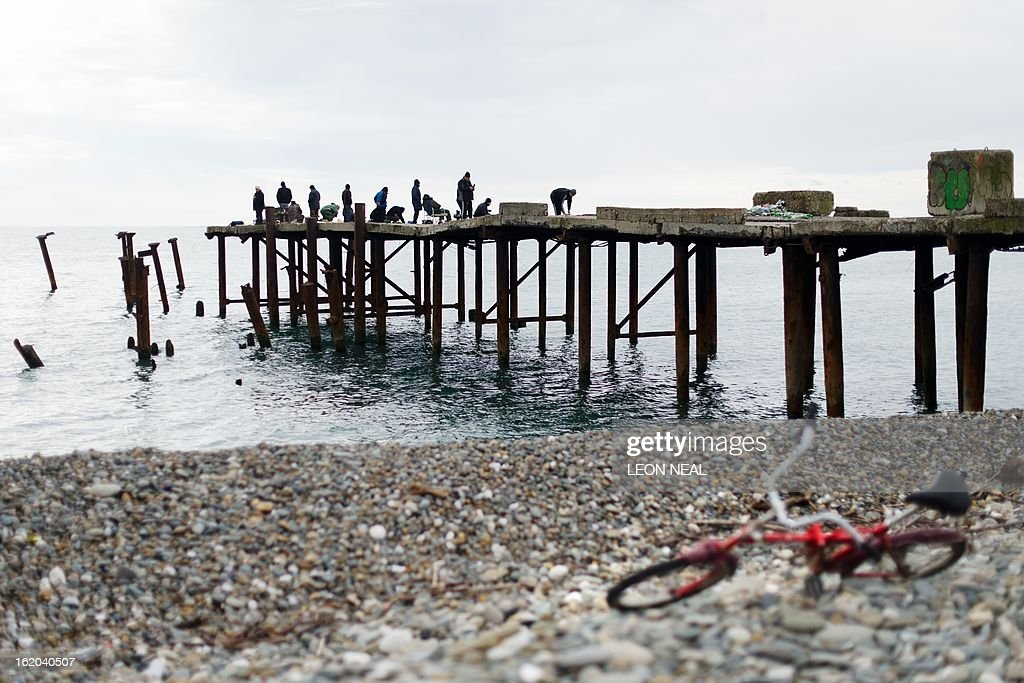 A bicycle lays on the beach near to a group of fishermen in Adler district of Sochi in Russia, on February 18, 2013. With a year to go until the Sochi 2014 Winter Games, construction work and development continues as Olympic tests events and World Championship competitions are underway.