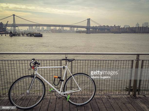 Bicycle locked to waterfront railing overlooking urban bridge, New York, New York, United States