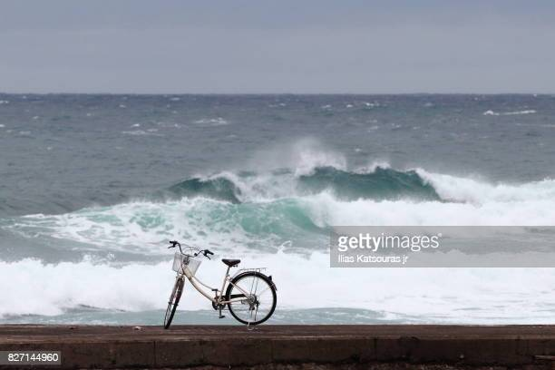 Bicycle on breakwater, with rough sea in the background