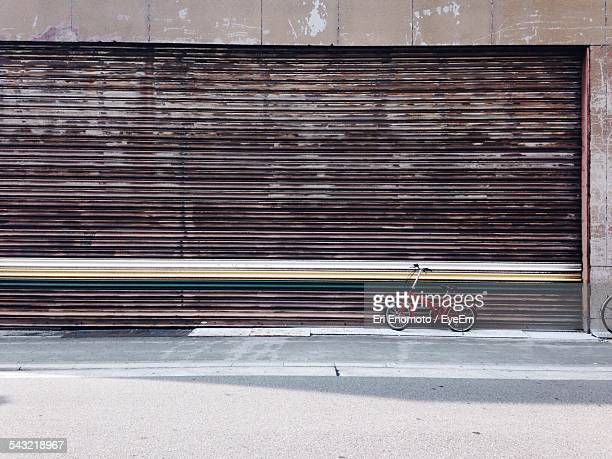 Bicycle Parked Against Closed Corrugated Shutter