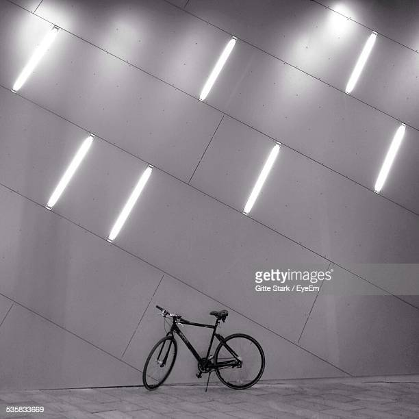 Bicycle Parked Against Illuminated Wall