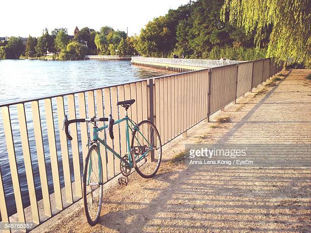 Bicycle Parked By Railing And Lake On Sunny Day