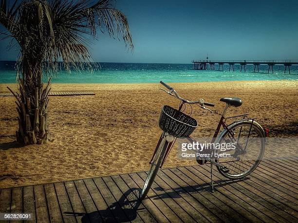 Bicycle Parked On Boardwalk In Front Of Sea Against Clear Sky