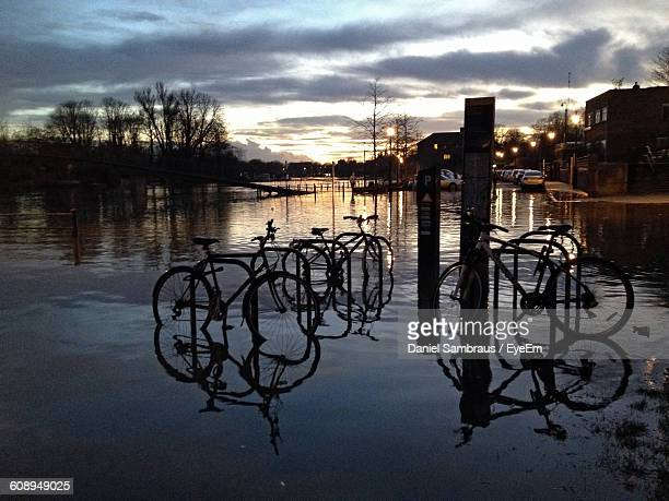 Bicycle Parked On Flooded Street Against Sky At Dusk