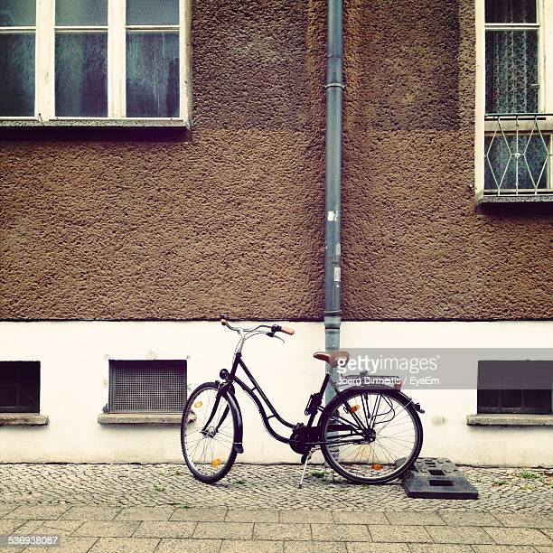 Bicycle Parked On Sidewalk Against Building In City