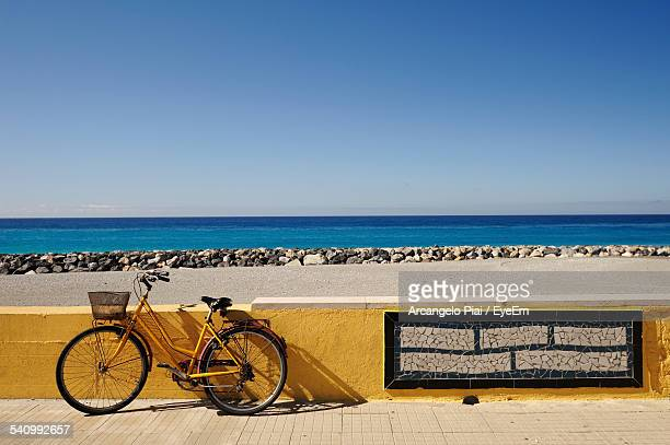 Bicycle Parked On Sidewalk By Wall At Beach