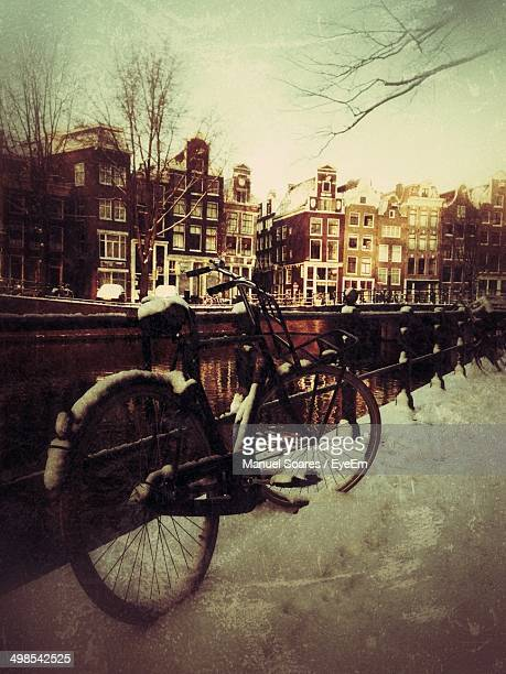 Bicycle parked with buildings in distance during winter