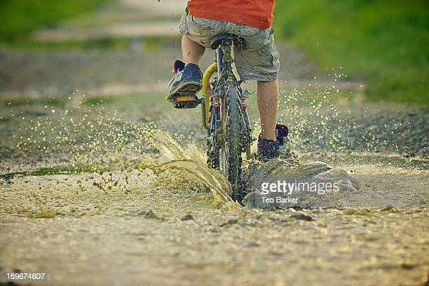 Bicycle passing by a puddle and splashing