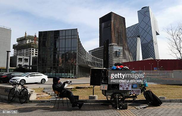 A bicycle repair man waits for customers at a streetcorner in Beijing on March 2 near the China Central Television Headquarters and the burnt...