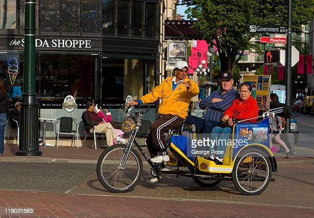 A bicycle rickshaw driver gives tourists disembarking from the cruise ships a tour on July 2 2011 in Victoria British Columbia Canada This coastal...