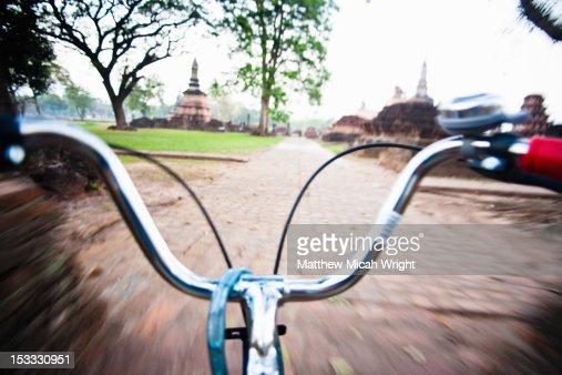 A bicycle ride through ancient Thai ruins. : Stock Photo