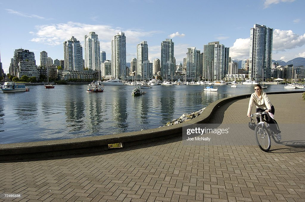 A bicycle rider enjoys the challenges of a serpentine walkway that runs along False Creek across the busy harbor from the skyscrapers of the downtown...