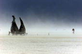 A bicycle rider makes it through a dense sand storm at Black Rock City's playa during the Burning Man Festival in Nevada 01 September 2000 An...