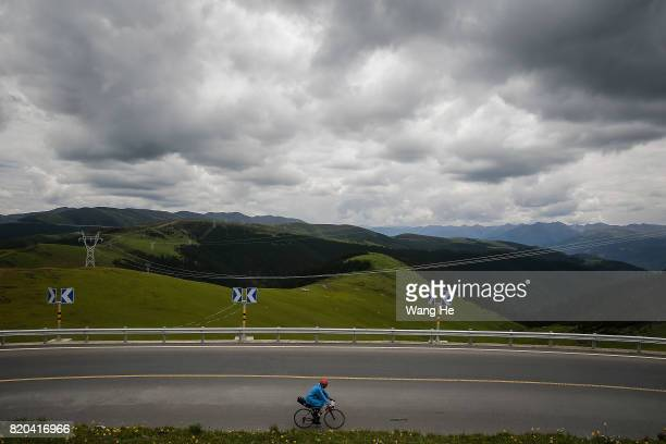 A bicycle rider on G318 nations road on July 21 2017 in Litang County Ganzi Tibetan Autonomous Prefecture Sichuan Province China Litang County known...