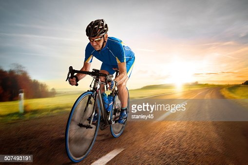 Bicycle Rider pedaling on a Country Road at Sunset