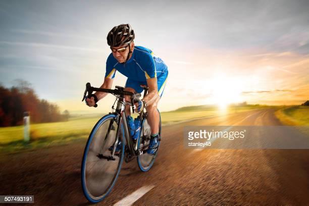 自転車ライダー pedaling で、Country Road の夕暮れ