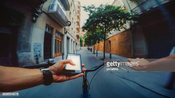 POV-Radfahren in der Stadt, während der Beratung einer Karte auf Handy