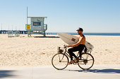 Bicycle riding with a surf on Venice Beach in october 2013