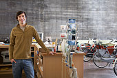 Bicycle shop owner standing at counter, smiling, portrait
