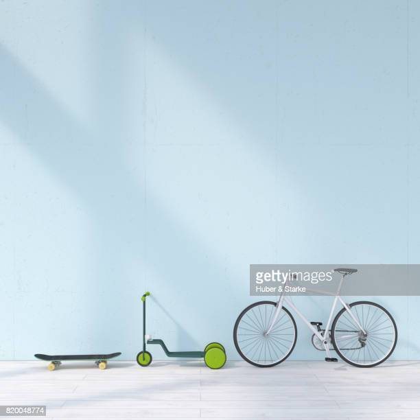 bicycle, skateboard, scooter leaning against wall