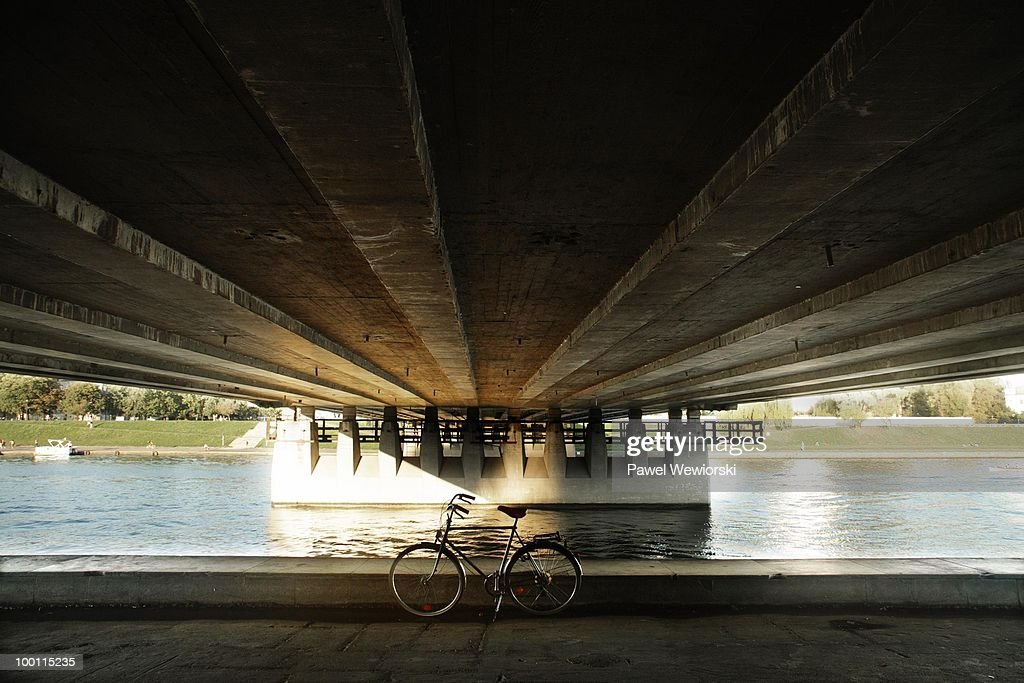 Bicycle standing under bridge : Foto de stock