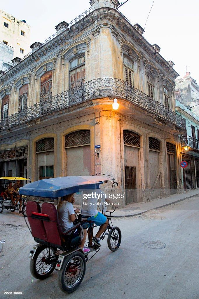 Bicycle taxi going down street in Havana, Cuba