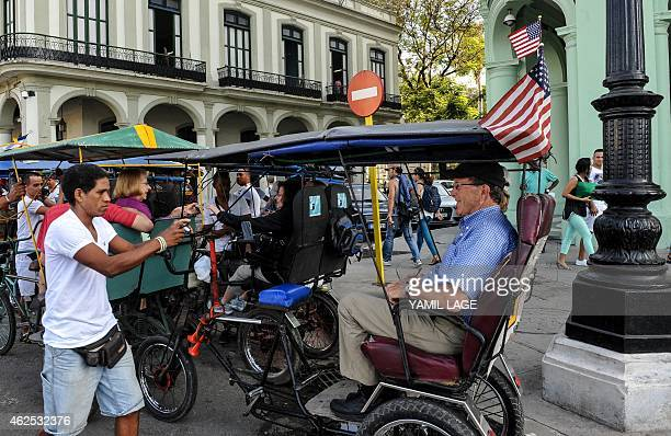 A bicycle taxi with a US flag takes tourists in a street of Havana on January 30 2015 AFP PHOTO/YAMIL Lage