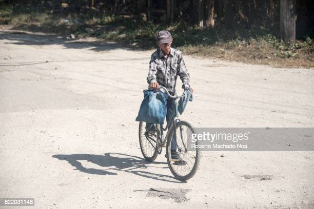 Bicycle use in Cuban countryside Cuban real people lifestyle Old man in checkered shirt and hat riding bicycle with blue bag on a lonely road on a...