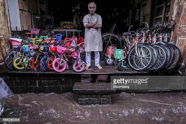 A bicycle vendor stands inside his store out of the rain as he waits for customers in Nashik Maharashtra India on Saturday Sept 12 2015 Millions of...