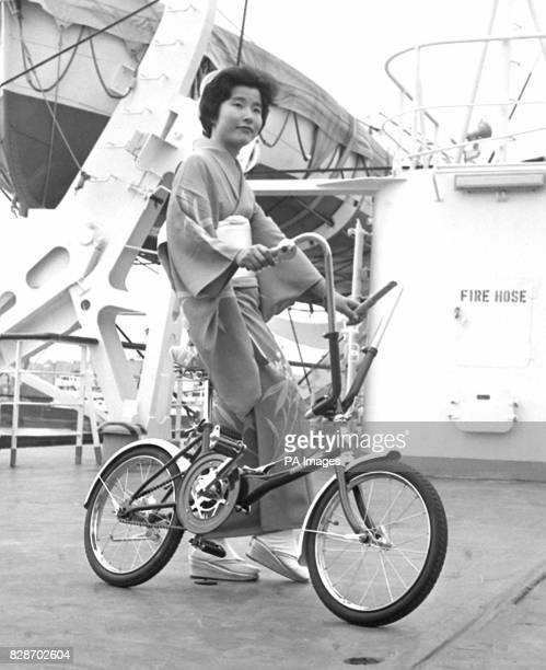 A bicycle which will fold down to the size of a handy suitcase and known as the Silk PortaCycle is demonstrated by traditionally dressed Chieko...