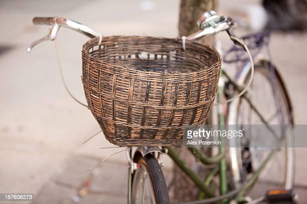Fahrrad mit einem braunen Weidenkorb auf Lenkergriffe.