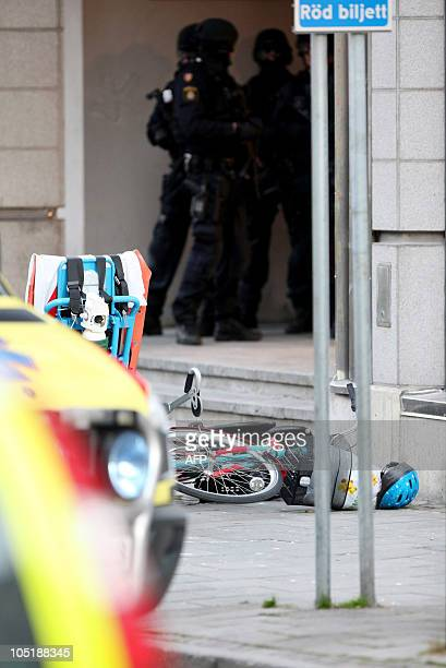 A bicycle with a child seat and helmet lays on the street in front of heavily armed police at in the entrance to a building on Storgatan in central...