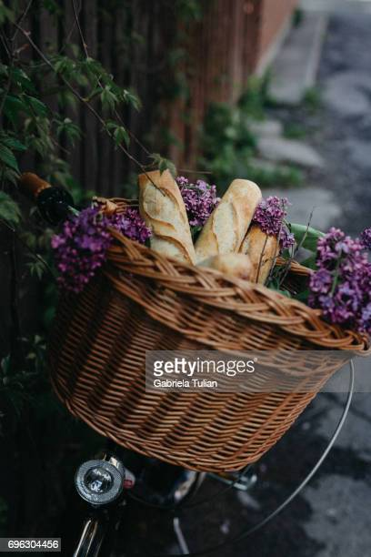 Bicycle with fresh bread and flowers in a basket