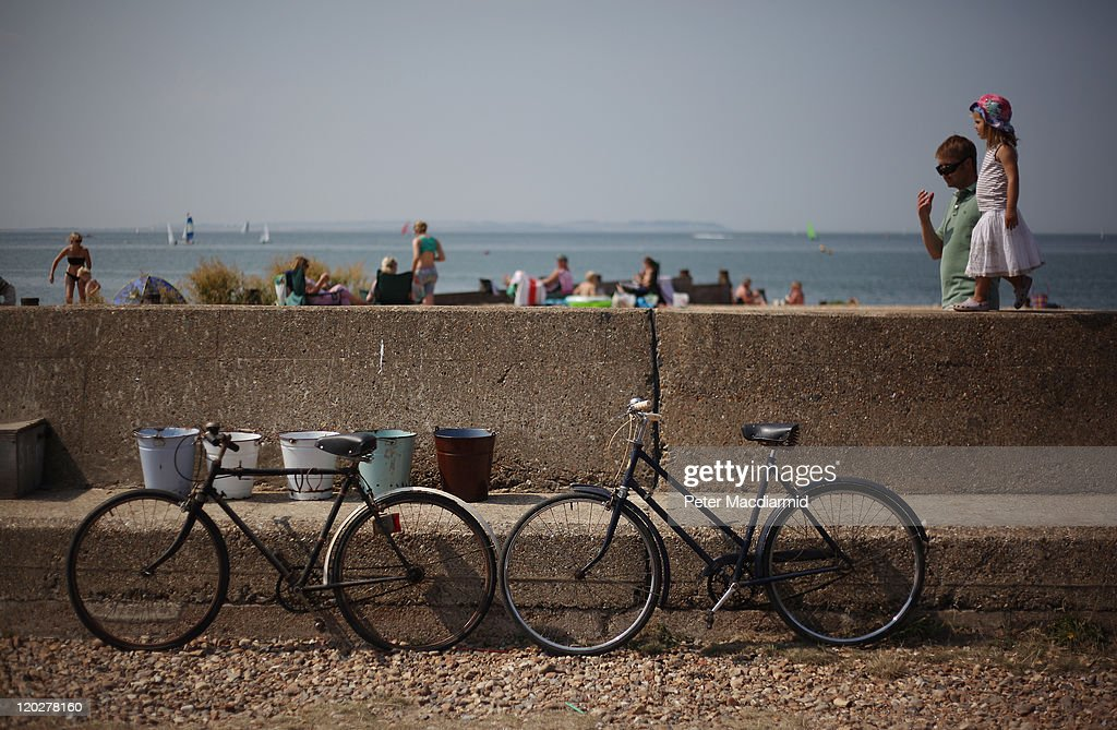 Bicycles and buckets are displayed for sale on a flood defence wall on August 3, 2011 in Whitstable, England. Parts of southern England are experiencing high summer temperatures.